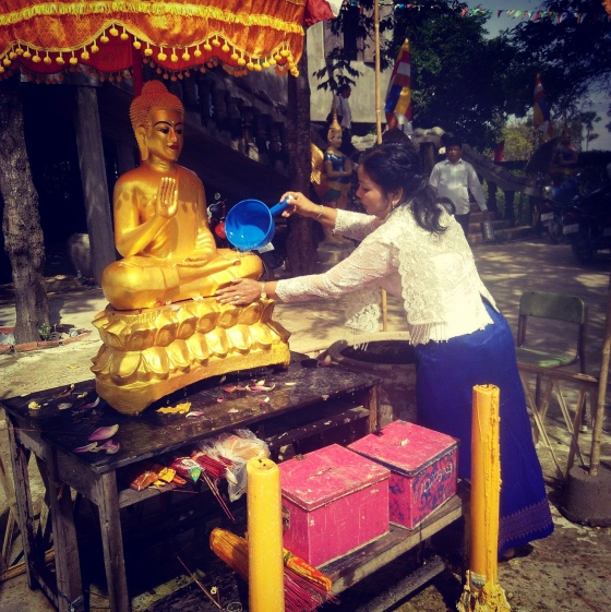 A Cambodian woman next to a religious statue