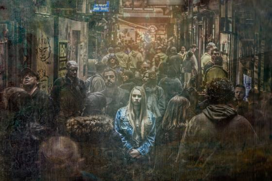 A drawing of a girl standing alone in a scary crowd.