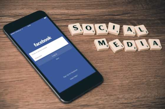 A phone with the Facebook login page open, next to a Scrabble game that says Social Media